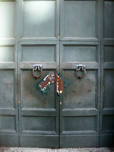 Green doors that are very worn around the keyhole.