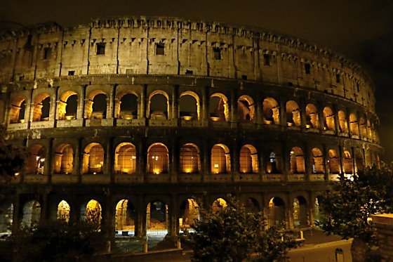 The Colosseum with lights in the archways and a spotlight on the side.