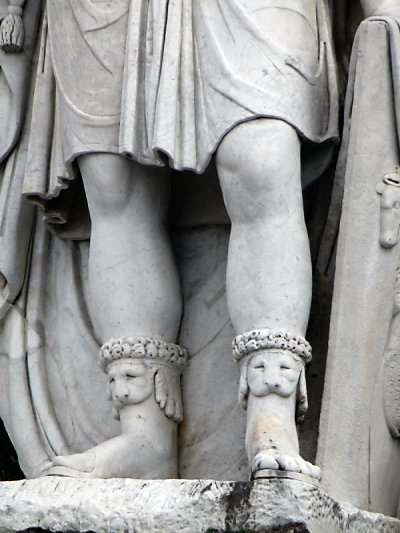 Toeless dog socks on a statue.